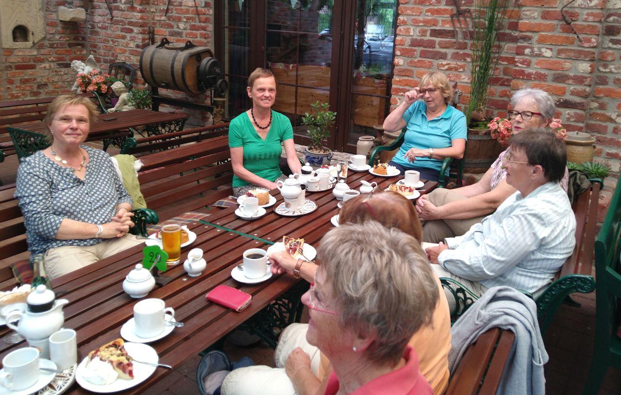 Einige Mitglieder des Südviertelhofes sitzen um einen gedeckten Tisch.