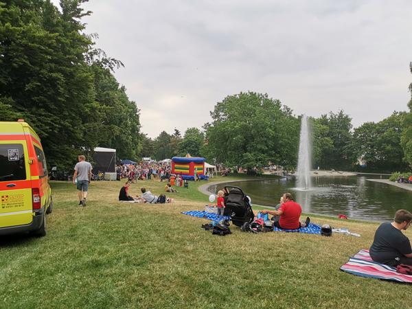 Suedviertelfest, Menschen sitzen am Teich mit Springbrunnen.